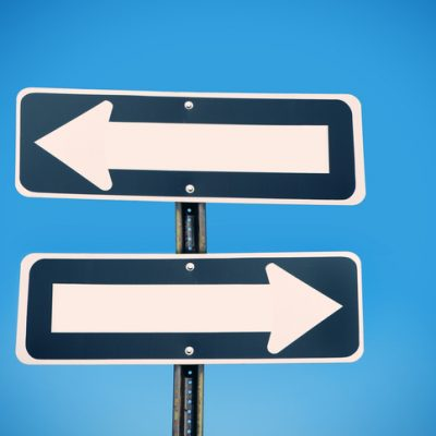 Two one way signs pointing in opposite directions.